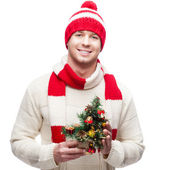 Young casual man in winter hat hoding christmas tree — Stock Photo