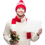 Young casual man in winter hat hoding christmas tree and sign — Stock Photo
