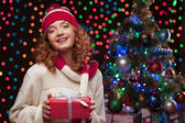 Young woman holding red gift over christmas tree and lights on b — Stock Photo