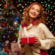 Young woman holding red gift over christmas tree and lights on b — Stock Photo #51458537