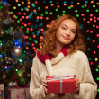 Young woman holding red gift over christmas tree and lights on b — Stock Photo #51458565