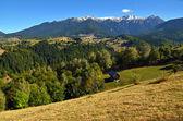 Maison dans la vallée avec des montagnes enneigées en arrière plan — Photo