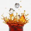 Splashing drink, glass, falling ice cubes — Stock Photo