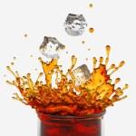 Splashing drink, glass, falling ice cubes — Stock Photo
