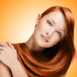 Woman with long red hair, isolated on yellow background — Stock Photo