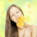 Beautiful woman holding autumn leaves — Stock Photo