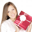 Happy beautiful woman in Santa hat holding Christmas gift — Stock Photo #13693828