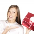 Happy beautiful woman in Santa hat holding Christmas gift — Stock Photo #13693845