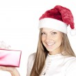Happy beautiful woman in Santa hat holding Christmas gift — Stock Photo #13693868