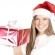 Happy beautiful woman in Santa hat holding Christmas gift — Stock Photo #13693875