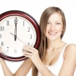 Stock Photo: Surprised attractive young woman holding big clock , isolated on white background