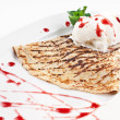 Close-up image of a delicious pancakes with ice-cream on it and strawberry syrup all over the plate — Stock Photo
