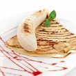 Close-up image of a delicious pancakes with banana on it and strawberry syrup all over the plate — Stock Photo