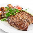 Image of a grilled steak with vegetables on a white plate - Stock Photo