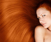 Fashion conceptual portrait of a woman with beautiful long red healthy shiny hair — Stock Photo