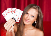 Beautiful young woman holding poker cards — Stock Photo