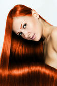 Beautiful young red-headed woman with long shiny hair — Stock Photo