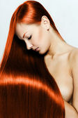 Beautiful young red-headed woman with long shiny hair — Zdjęcie stockowe