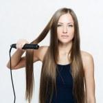 Beautiful woman hoding hair iron — Stock Photo