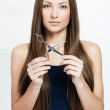 Beautiful young woman with long shiny hair holding scissors — Stock Photo #14343629