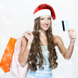 A portrait of a beautiful woman wearing Santa hat and holding shopping bags — Foto Stock