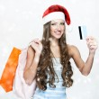 A portrait of a beautiful woman wearing Santa hat and holding shopping bags — Foto de Stock