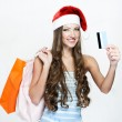 A portrait of a beautiful woman wearing Santa hat and holding shopping bags — Stock Photo #15648507
