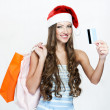 A portrait of a beautiful woman wearing Santa hat and holding shopping bags — Stock Photo