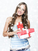 Young smiling woman holding Christmas present — Stock Photo