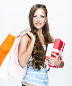 Beautiful woman with christmas present and shopping bags — Stock Photo