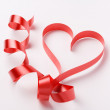 Red ribbon forming heart — Stock Photo