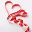 Red ribbon forming valentine's hearts — Stock Photo