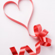 Red ribbon forming valentine's heart — Stock Photo #18236819