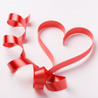 Red ribbon forming valentine's heart — Stock Photo #18236833