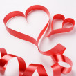 Red ribbon forming two valentine's hearts — Stock Photo