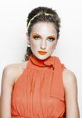 Portrait of a beautiful woman in orange dress — Stock Photo