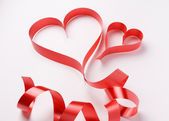 Red ribbon forming two valentine's hearts — Foto Stock