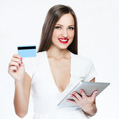 Smiling woman holding credit card and tablet pc — Stock Photo