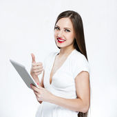 Smiling woman holding tablet pc and showing thumbs up — Stock Photo