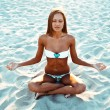 Yoga woman in lotus pose on beach at sunset — Foto de Stock