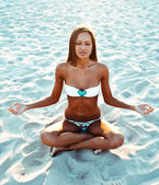 Yoga woman in lotus pose on beach at sunset — Stock Photo