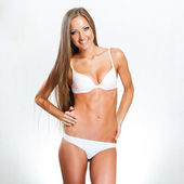Beautiful young long-haired girl in white underwear — Stock Photo