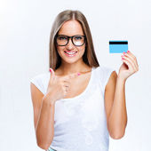 Portrait of smiling business woman in black horn-rimmed glasses with credit card — Stock Photo