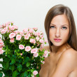 woman with beautiful face and pink flowers — Stock Photo