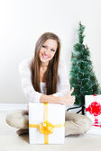 Woman with christmas gifts thumbs up — Stock Photo