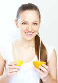 Attractive smiling young woman drinking orange juice straight from fruit — Stock Photo