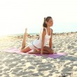 Attractive girl doing yoga on the beach — Stock Photo #51409791