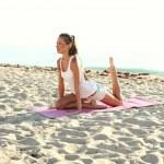 Attractive girl doing yoga on the beach — Stock Photo #51409795