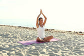 Attractive girl doing yoga on the beach — Stock Photo