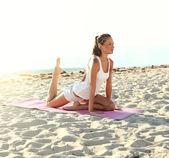 Atrakcyjna dziewczyna robi jogi na plaży — Zdjęcie stockowe